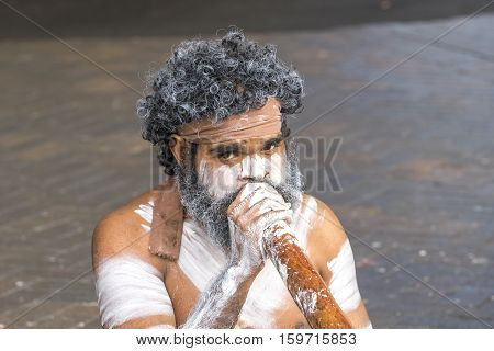 SYDNEY AUSTRALIA - AUGUST 26 2016: Unidentified body painted aborigine street musician playing on his traditional didgeridoo at Circular quay in Sydney Australia.