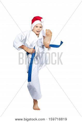 In cap of Santa Claus karateka hits kick leg forward