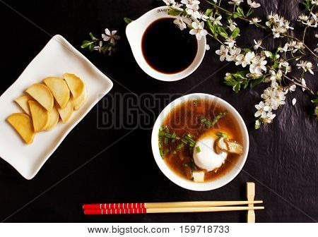 Miso soup with egg, tofu, mushrooms, seaweed, daikon slices and soy sauce on the black table with flowers