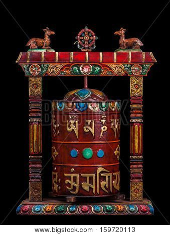 A prayer wheel brightly decorated with the mantras topped with a wheel of teaching - dharmachakra and two deers. Handwork it is isolated on a black background.