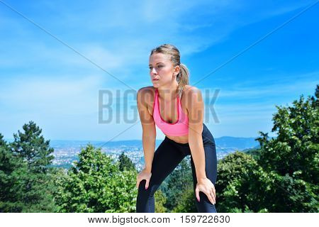 Sweaty fitness woman tired after training. Caucasian female athlete sweating and exhausted after exercising on sky copy space background.