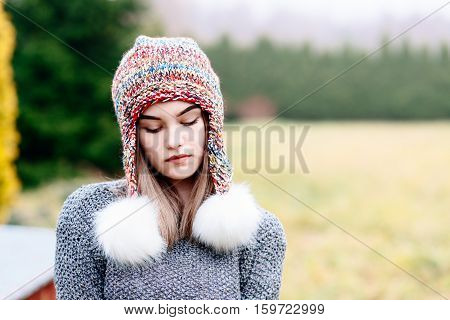 Thoughtful Young Woman In Colorful Woolen Cap