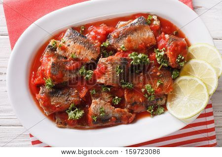 Tasty Sardines In Tomato Sauce With Lime And Parsley Close-up. Horizontal Top View