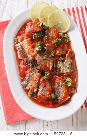 Tasty Sardines In Tomato Sauce With Lime And Parsley Close-up. Vertical Top View
