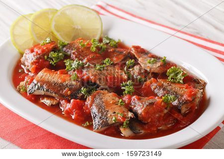 Braised Sardines In Tomato Sauce With Lime And Parsley Close-up. Horizontal