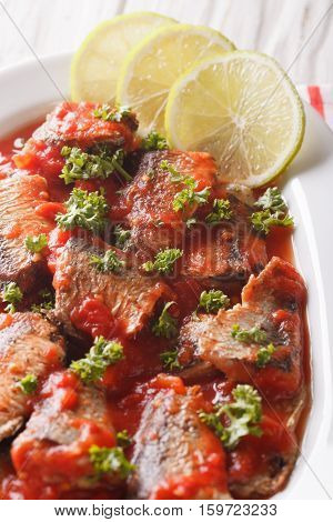 Sardines In Tomato Sauce, Decorated With Lime And Parsley Close-up. Vertical