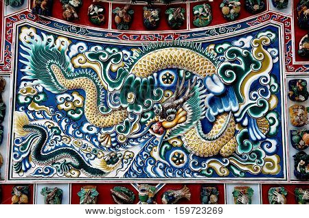 Bang Pa-In Thailand - December 28 2009: Detail of the ceramic Dragon Screen at Phra Thinang Wehat Chamrun Chinese Pavilion at the Bang Pa-In Royal Summer Palace