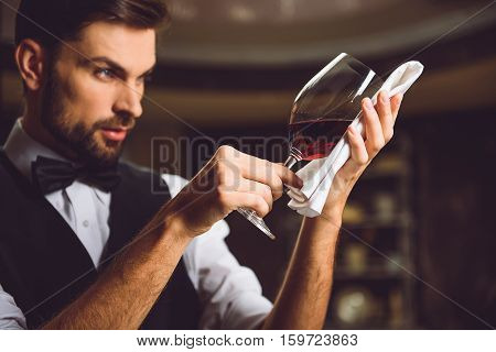 Wineglass with scarlet nectar against napkin in hands of sommelier