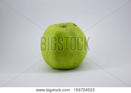 green, juicy, slightly bruised apple on a white background