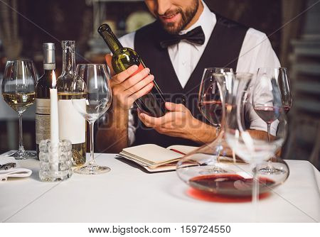 Softly smiling man is sitting at table and carrying bottle of crimson nectar