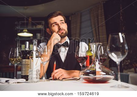 Gourmet is sitting at served wine table. He dreaming with smile at his face