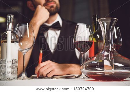 Thoughtful man is sitting at table and holding pen. Focus on carafe and glasses with scarlet drink