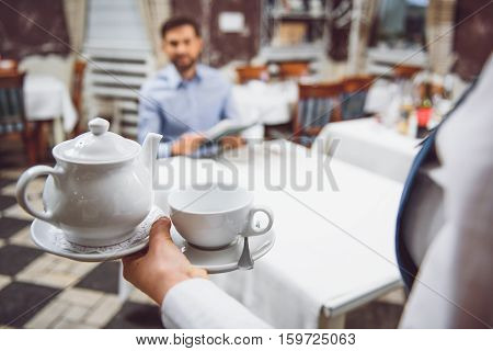 Smiling man is sitting at table, waiting for full teapot with calyx. Focus on ceramic teakettle and chalice