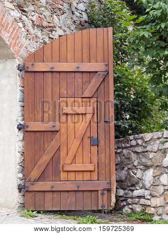 Half of open wooden gate with wicket