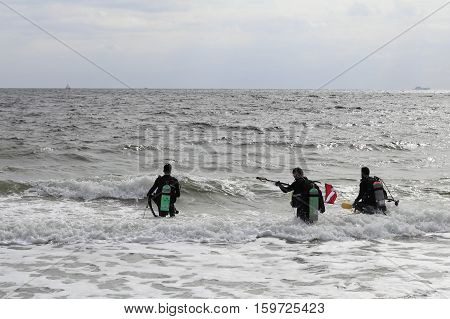 Fort Lauderdale FL USA - March 5 2016: Three male scuba divers walk into the Atlantic Ocean to go diving. Divers with full gear head into the ocean to go diving