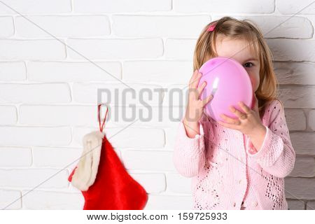 young cute little blonde girl in pink sweater holding balloon with decorative christmas or xmas stocking or boot on white brick wall background copy space