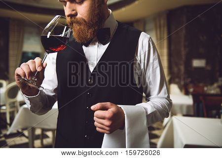 Sommelier is staying, taking glass with scarlet nectar and smelling it. His eyes are closed in thoughtfulness