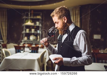 Bearded sommelier is holding glass of nectar and inhaling smell with pleasure