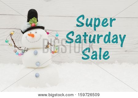 Super Saturday message Some snow and a snowman on weathered wood with text Super Saturday Sale