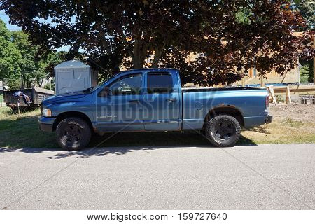 HARBOR SPRINGS, MICHIGAN / UNITED STATES - AUGUST 2, 2016: A Dodge Ram 1500 pickup truck is parked in the shade outside of a construction site in Harbor Springs.