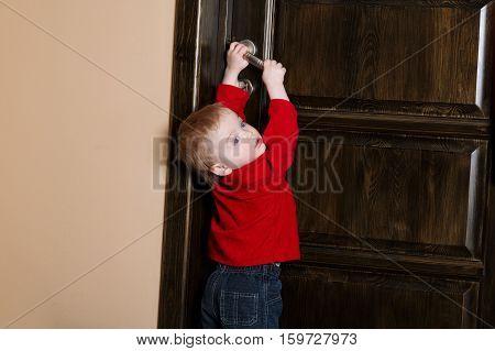 little boy tries to open door at home