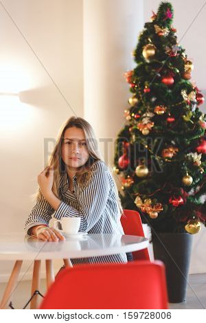 Portrait of a beautiful girl with a cup of coffee in a cafe with Christmas decorations.