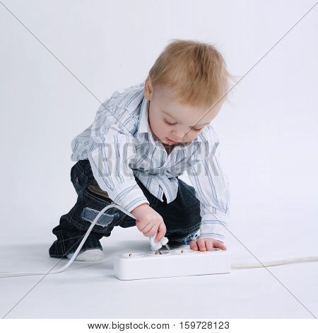 little boy plays with plug on white background