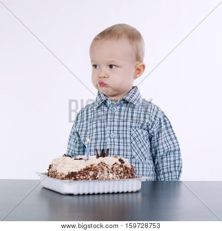 photo of cute little boy with birthday cake on white