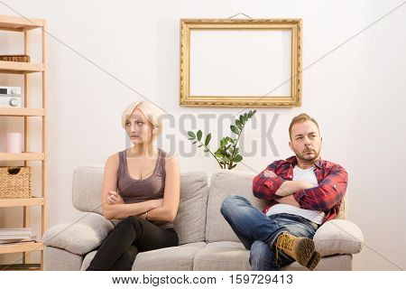 Offended couple man and woman do not speak at home. Man and woman sitting on sofa or couch with their arms crossed or folded. Sad, disappointed, angry.