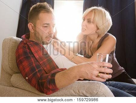 Couple man and woman having conflict concerning alcohol drinks while spending free time at home. Blond wife screaming at her husband and touching him. Quarrel concept.