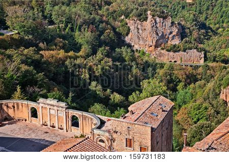 Sorano, Grosseto, Tuscany, Italy: the square of the source and aqueduct with view of the forest and the rock face with caves carved into the tufa