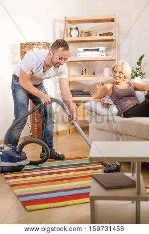 Handsome man using vacuum cleaner while his wife resting and relaxing at home atmosphere. BLond wife smiling to her husband. Family concept.