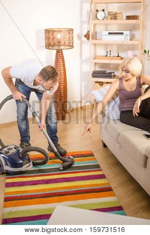 Blond wife made her handsome man using vacuum cleaner for cleaning floor in house. Man helping his wife with household things at home. Family concept.