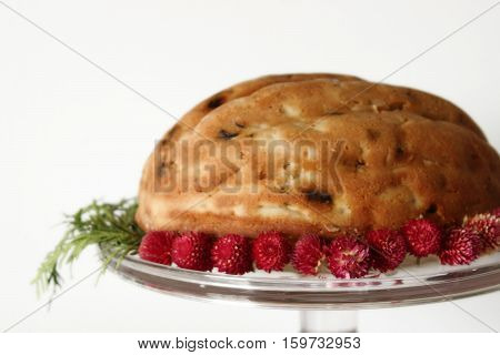 Close up of a fruitcake on cake stand. Flowers and greens decorate the cake stand.