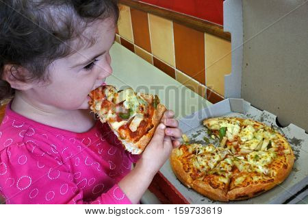 Little child (girl age 2) eats fast food. Children healthcare concept. Real people. Copy space