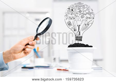 Hand of business person examining with magnifier sketched plan for income growth