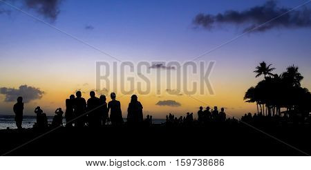 Hawaii, USA - Dec 21, 2015: People come out the enjoy the famous Waikiki sunset in Honolulu. Hawaii is reknown for sunsets with intense colors.