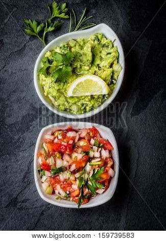 Traditional mexican Latin American sauces - avocado sauce Guacamole, tomato sauce Salsa in white bowls on stone slate background