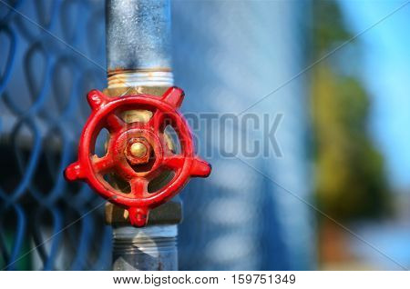 A selective focus image of a red shut off valve against a chain link fence.