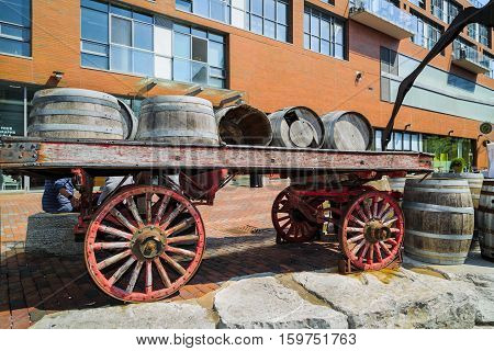 Toronto, Ontario, Canada, May 22, 2016, nice gorgeous amazing closeup view of vintage classic horse drawn carriage loaded with wooden barrels at Toronto historic distillery district on art fest day
