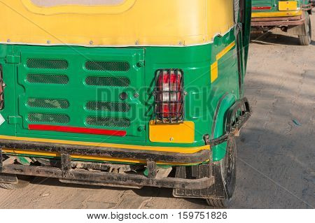 The back side of traditional motorized rickshaw or tuk tuk taxi on the street in Agra India
