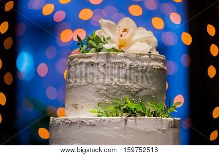 Split-level Wedding Cake With Natural Flowers On Bokeh Background
