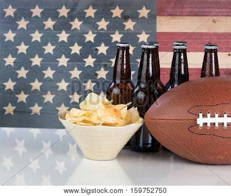 Football potato chips cold beer in bottles on white glass table with United States flag painted on rustic wood. Layout in horizontal format with copy space.