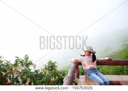 Young Asian girl in little cowboy costume (North plaid shirt blue jeans and Sombrero hat) sitting on wood balcony with mountain landscape and sea of mist. Phutabberk Petchabun Thailand. Copy space.