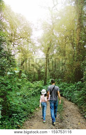 Father and daughter hand in hand walking during the hiking activities in rain forest with sunlight. Fathers day concept Phuphangmar phuhin rongkla national park Petchabun Thailand.