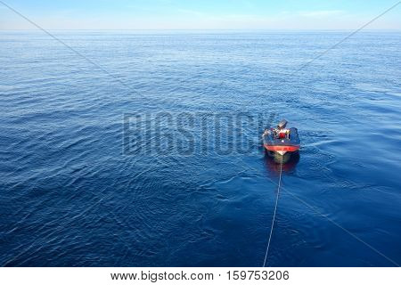 Dinghy boat mooring on ocean with Calm and smooth sea. Dinghy boat waiting for scuba divers. copy space.