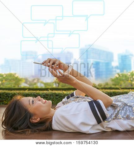 city life style of asian woman lying and touching on mobile phone screen against green environment and urban skylind background