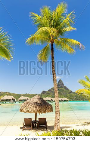 Two sunlounger chairs under a thatched parasol on a sand beach with a view on the lagoon and Mount Otemanu on the tropical island of Bora Bora near Tahiti in French Polynesia.