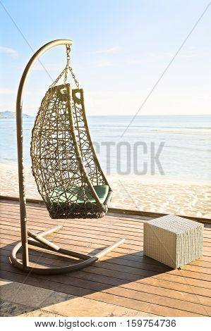 Cozy hanging resting chair on decking by sea side at evening sun light vertical composition