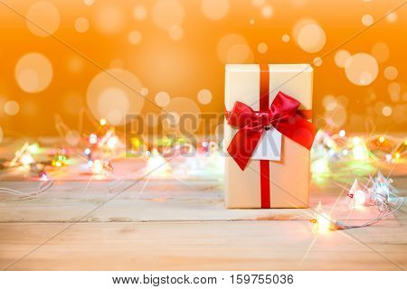 Cream colored gift box tied with red bow and blinker on wooden background